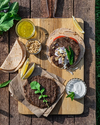 Spicy lamb kebab patties served with mint dip, crunchy salad, pitta bread and raw red onions
