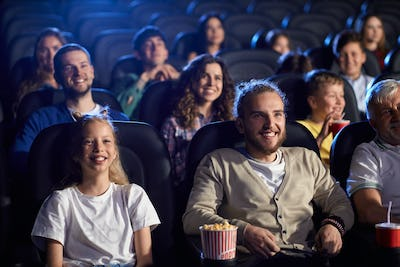 Young man with younger sister in cinema
