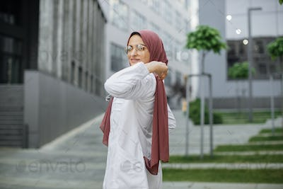 Muslim doctor or nurse woman in white coat, adjusting her hijab and looking at camera