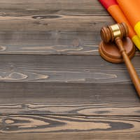 Woden judge mallet symbol of law and justice with lgbt flag in rainbow colours on wooden background