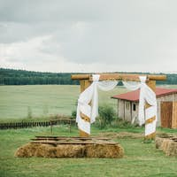 Wedding ceremony outside on a green lawn in a rustic style.Decor with arches of fresh flowers for