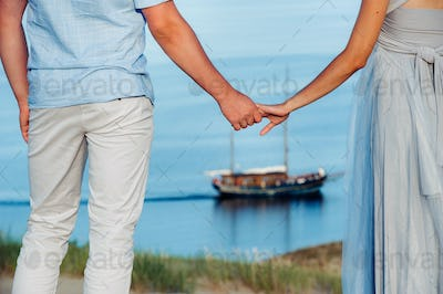 A couple in love stands on the beach in the dunes against the background of the Baltic sea and a