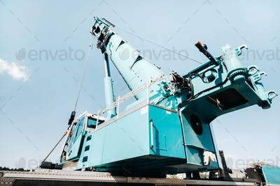 a cab with the operator of a Large blue car crane that stands ready to operate on hydraulic supports