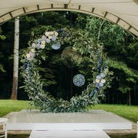 Wedding ceremony on the street on the green lawn.Decor with fresh flowers arches for the ceremony
