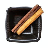 two sticks of cassia cinnamon in bowl isolated