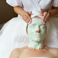 Experienced cosmetician removing alginate mask from a face of a caucasian woman