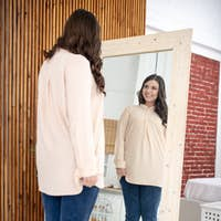 Young woman in a beige blouse standing on a weigher and looking at herself
