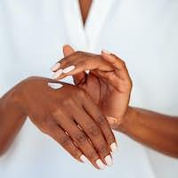 Black mature woman applying hand cream