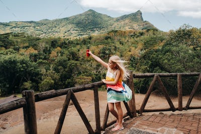 a little girl with a red can of drink in her hands against the background of the mountains of the