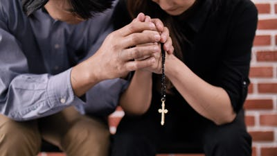 A young Asian Christian couple praying to Jesus Christ in a church.
