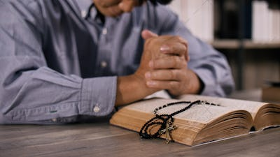 A young Asian Christian man praying to Jesus Christ in a church.