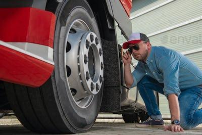 Trucker Looking on Semi Truck Wheel