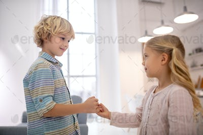 Boy and girl clenching little fingers and smiling