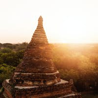 Buddhist temple shape against sun light during sunrise