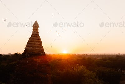 Buddhist temple shape against sun light during sunrise.