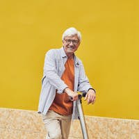Mature Man Riding Scooter on Yellow