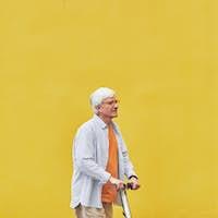 Senior Man Riding Scooter on Yellow