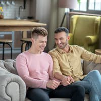 Two young men sitting on the sofa and smiling