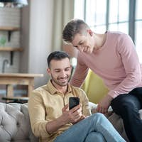 Gay couple looking enjoyed talking with friends online