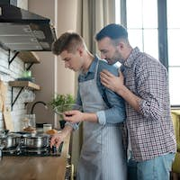 Two young men standing by the hob in the kitchen.