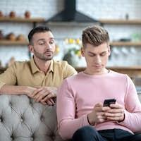 Man in orange shirt watching his partner chatting online