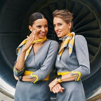 Two air hostesses in uniforms conversing by the aeroengine