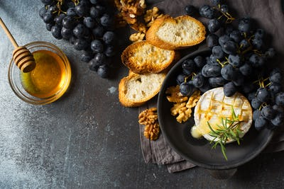 Roast camembert and honey with black grapes and baked slice of bread on dark background