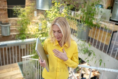 Blonde woman standing on stairs, holding laptop, feeling sick