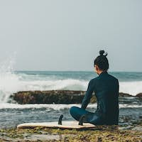Woman surfer sit on reef looking at the waves
