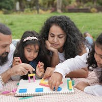 Indian parents having playful time with children at city park