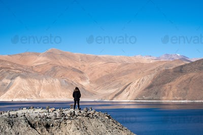 A woman standing in front of Pangong lake with mountains view and blue sky background