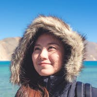 Portrait image of a beautiful Asian woman standing in front of Pangong lake , Ladakh India