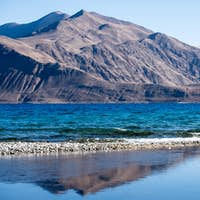Landscape reflection image of Pangong lake with mountains view and blue sky background