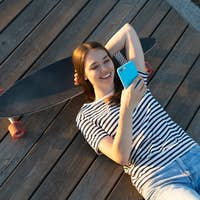 Young girl chatting with friends online smiling use smartphone relaxed lying outdoors on longboard
