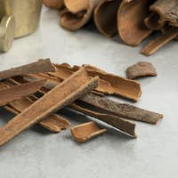Dried Cinnamon bark close up in front of a traditional mortar and pestle