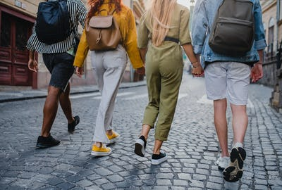 Rear view of group of young people outdoors on trip in town, walking and holding hands