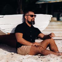 Portrait of a beautiful brutal man, enjoying and relaxing, sitting on the beach of the island of