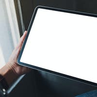 Mockup image of a woman holding black tablet pc with blank white screen in cafe