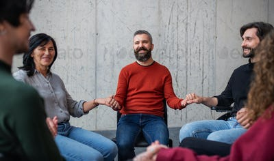 Men and women sitting in circle during group therapy, holding hands