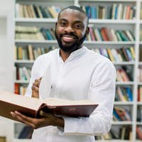 Smiling joyful male african american university student standing in modern reading hall of college