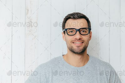 Handsome male with dark hair, wears spectacles, has gentle smile, looks directly into camera