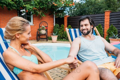 couple on beach chairs holding hands while spending time near swimming pool on backyard on summer