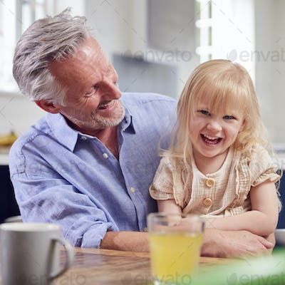 Grandfather Looking After Laughing Granddaughter Sitting At Kitchen Table