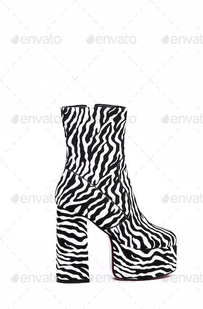 Stylish zebra boots shoes in white space. Minimal still life scene. Sale and shopping trendy concept