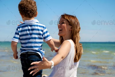 Young Mom Enjoys the Beach with Son