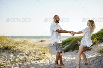 Young happy couple holding hands and walking together to the beach on summer day