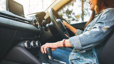 Closeup image a female driver shifting automatic gear stick while driving car