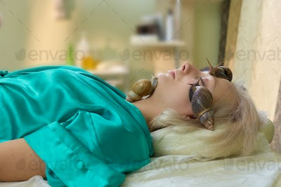 Young woman receiving snail facial massage.