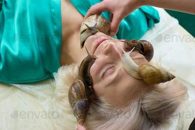 Snails on female face in spa salon.