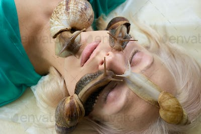 Woman receiving facial massage with snails.